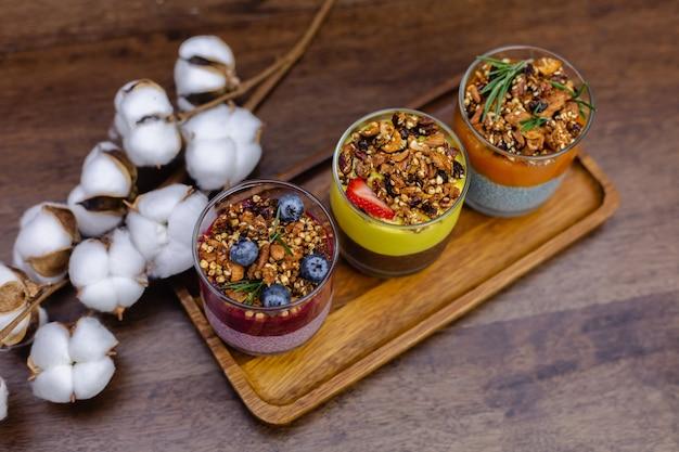 Kleurrijke gezonde ontbijt zoete woestijnen paar verschillende chia puddingen in glazen potten op houten tafel in de keuken thuis.