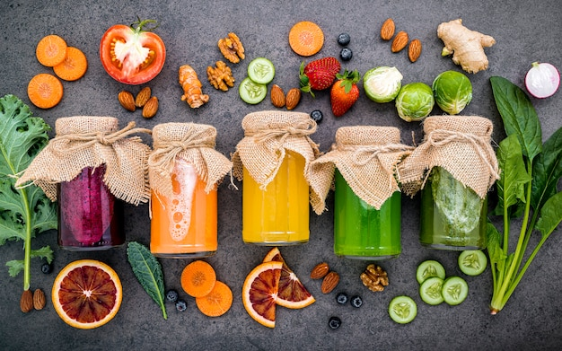 Kleurrijke gezonde smoothies en sappen in flessen met vers tropisch fruit en superfoods op donkere steen