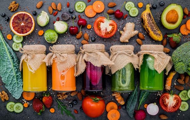 Kleurrijke gezonde smoothies en sappen in flessen met vers tropisch fruit en superfoods op donkere steenachtergrond met exemplaarruimte.