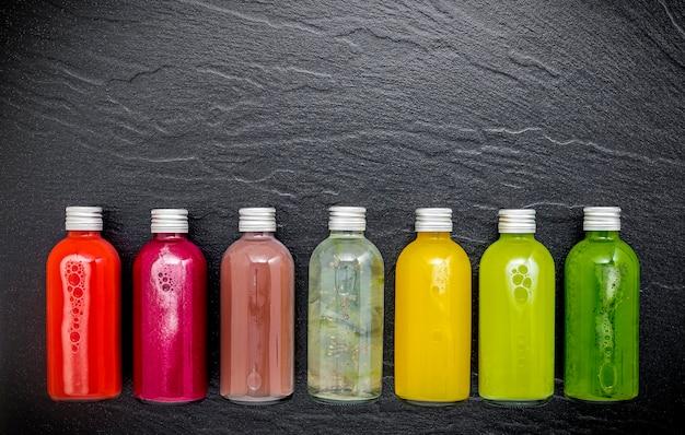 Kleurrijke gezonde smoothies en sappen in flessen op donkere steenachtergrond met exemplaarruimte.