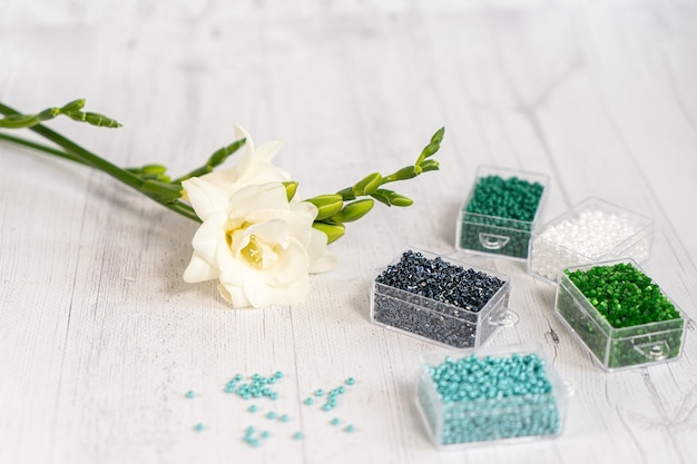 Kleurrijke glaskralen met bloemen. een verscheidenheid aan vormen en kleuren om een kraal of een kralenketting voor vrouwen te maken