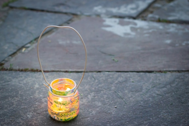 Kleurrijke glazen pot met draadhandvat kaarslamp op stenen buitentegel kinderactiviteiten en handgemaakt