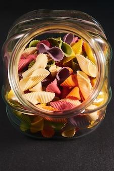 Kleurrijke glazen pot vol conchigliette pasta