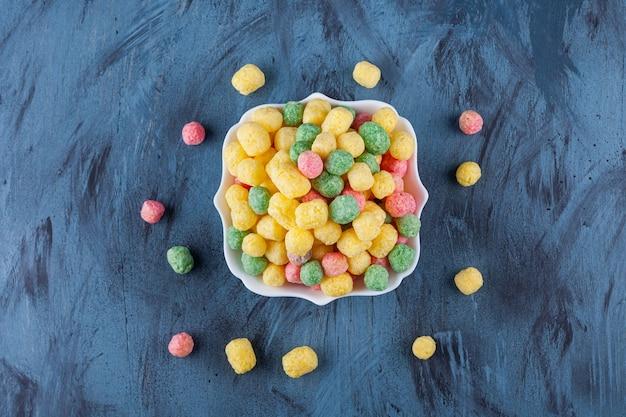 Kleurrijke graanballen die in een wit bord worden geplaatst.