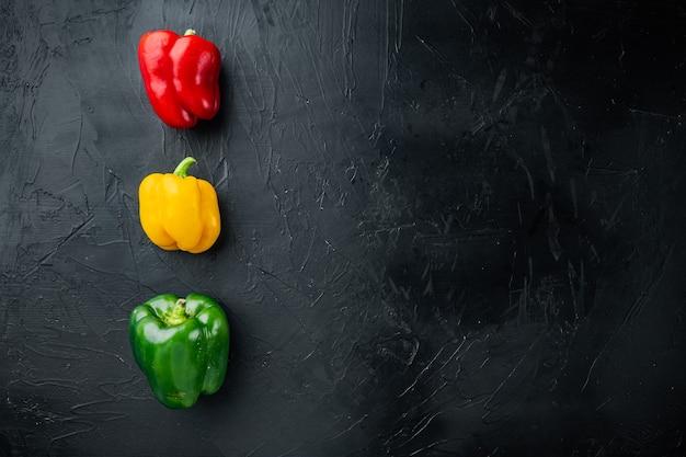 Kleurrijke groene, rode en gele paprika's, op zwarte achtergrond, bovenaanzicht plat lag met kopie ruimte voor tekst