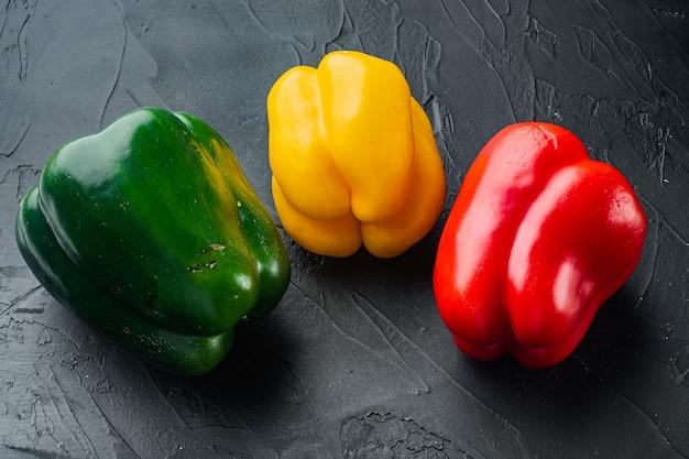 Kleurrijke groene, rode en gele paprika's, op zwarte achtergrond