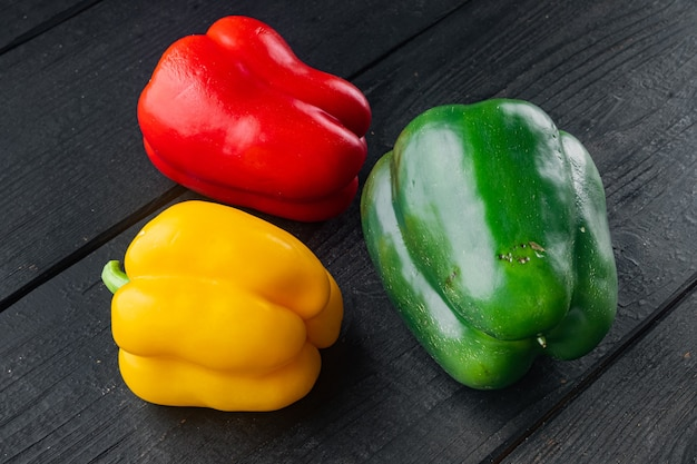 Kleurrijke groene, rode en gele paprika's, op zwarte houten tafel achtergrond