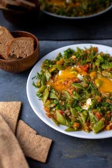 Kleurrijke groenten gekookt verschillende samen met brood op grijs bureau