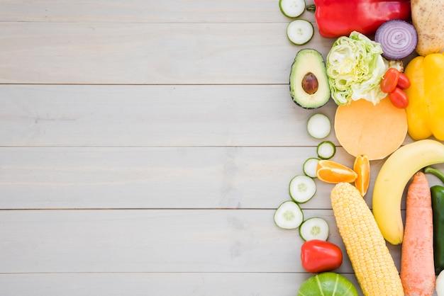 Kleurrijke groenten op houten bureauachtergrond