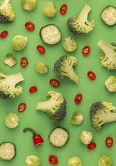 Kleurrijke groenten voedselpatroon gemaakt van broccoli, spruitjes, komkommer, chili peper, groene achtergrond. minimaal plat ontwerp over voeding, gezond eten, diëten, vitamines. bovenaanzicht