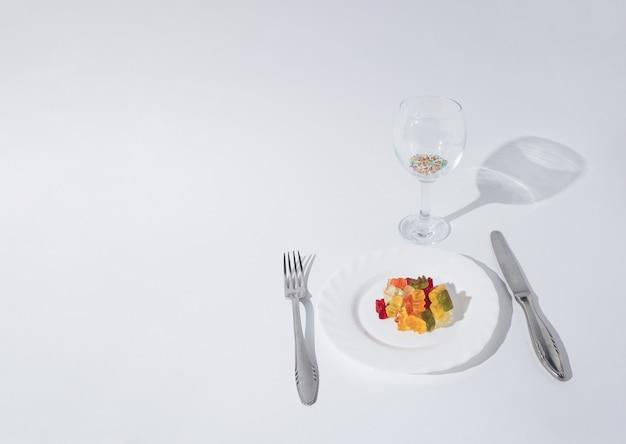 Kleurrijke gummyberen geserveerd op bord en glas vol kleurrijke snoepjes. minimaal creatief concept op witte achtergrond.