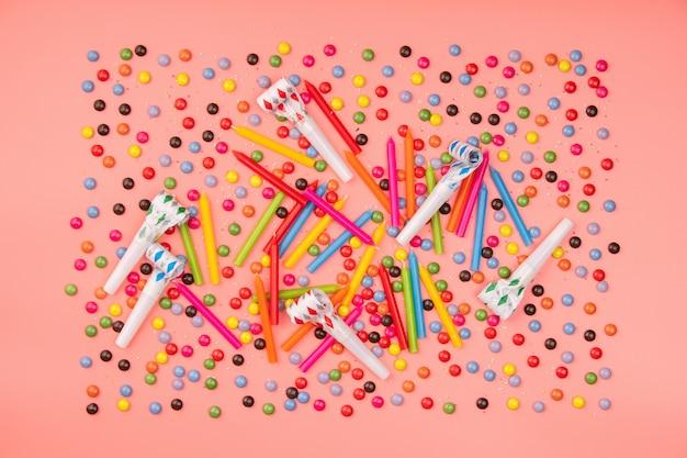 Kleurrijke hagelslag, blowers en verjaardagskaarsen op roze achtergrond