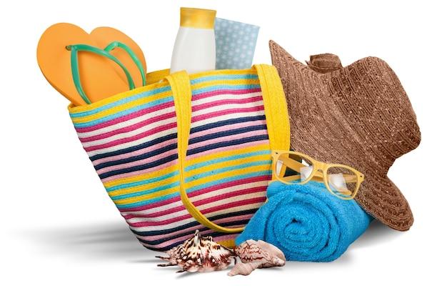 Kleurrijke handdoeken, cosmetica flessen en zeep in mand, geïsoleerd op wit