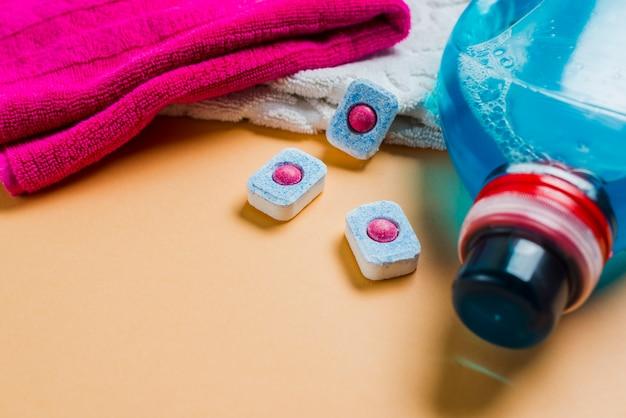 Kleurrijke handdoeken en vloeibaar wasmiddel met vaatwastabletten