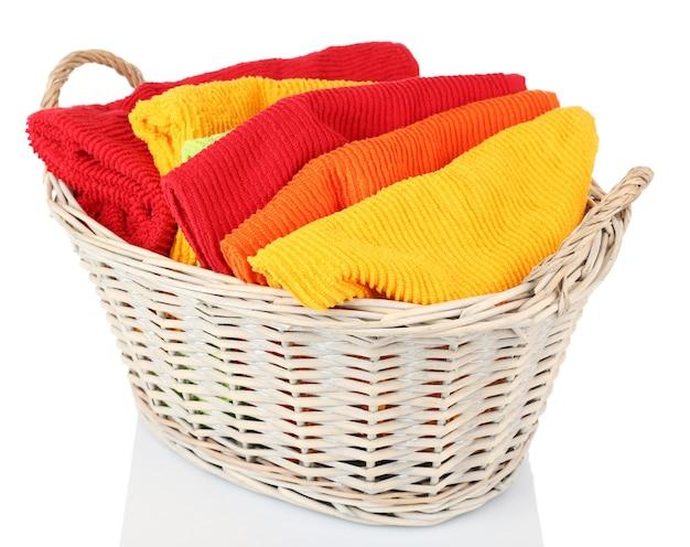 Kleurrijke handdoeken in mand op wit