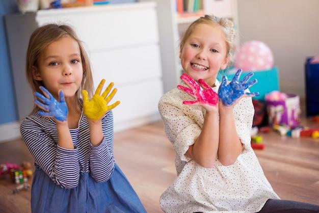 Kleurrijke handen gepresenteerd door schattige meisjes