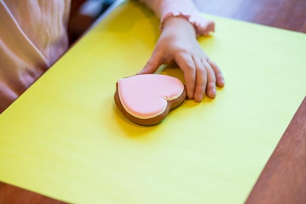 Kleurrijke handgemaakte pasen-objecten, bakkerij, koekjes op tafel en handen met beschilderd, versierd klein, klein koekje. kinderen versieren peperkoekkoekjes voor mam. gelukkige moederdag.