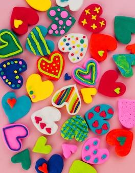 Kleurrijke handgemaakte plasticine harten op roze