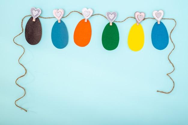 Kleurrijke handgemaakte wenskaart pasen gemaakt van paaseieren uit hun veelkleurige papier opknoping op een touw op wasknijpers op een blauwe achtergrond gesneden
