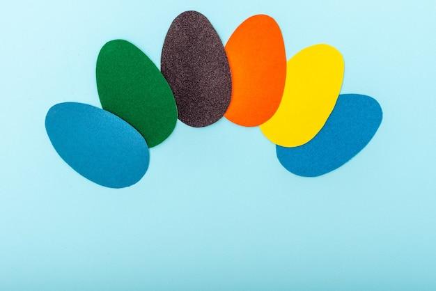 Kleurrijke handgemaakte wenskaart van pasen gemaakt van paaseieren vorm uitgesneden door hun veelkleurige papier op een blauwe achtergrond