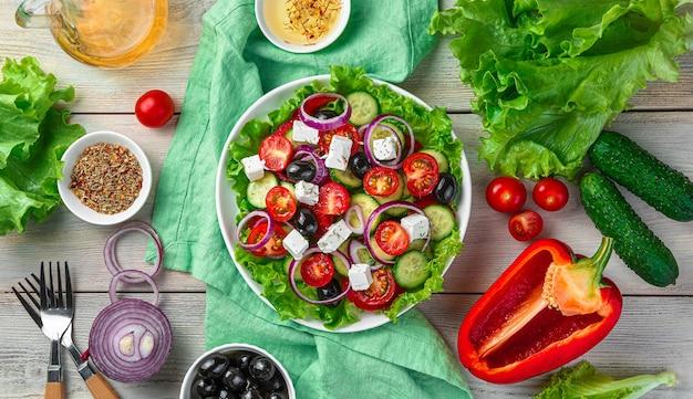 Kleurrijke, heerlijke griekse salade op een lichte houten achtergrond met ingrediënten. bovenaanzicht, horizontaal. het concept van culinaire achtergronden.