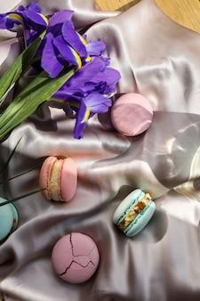 Kleurrijke heerlijke zelfgemaakte traditionele franse macarons - elegant frans dessert. natuurlijke fruit- en bessenaroma's, romige vulling en blauwe irisbloemen op doek voor valentijnsdag moederdag pasen.