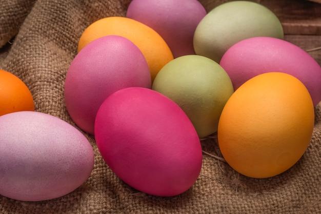 Kleurrijke heldere paaseieren op een jutetafel.
