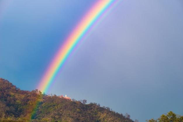Kleurrijke heldere regenboog aan de hemel. tempel op de heuvel.