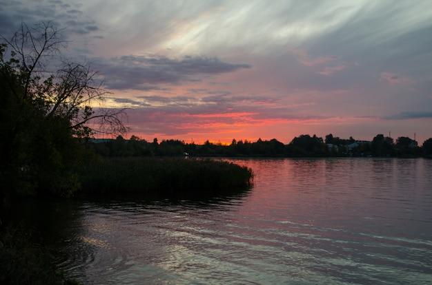 Kleurrijke hemel en kleurrijk water in meer dat in avond wordt weerspiegeld