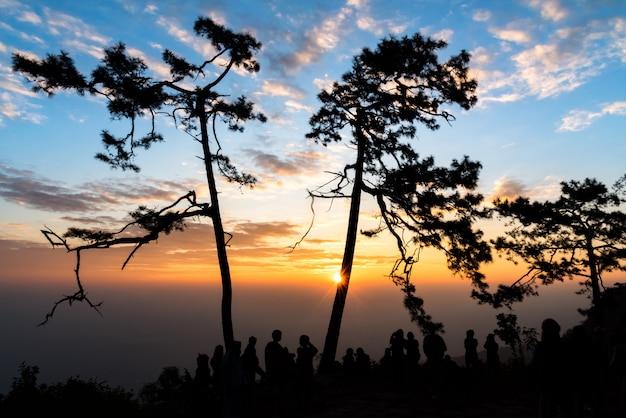 Kleurrijke hemel en silhouet van mensen die zonsopgang zien bij het nationale park van phukradueng, thailand.