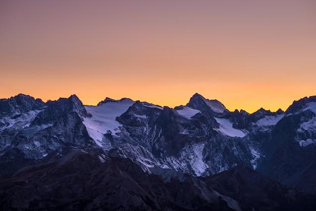 Kleurrijke hemel in de schemering voorbij de gletsjers op de majestueuze toppen van het massif des ecrins (4101 m), frankrijk. telelensweergave vanuit de verte op grote hoogte. heldere oranje lucht.