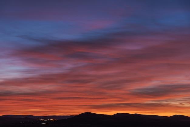 Kleurrijke hemel met roodachtige en blauwe tinten over het silhouet van sommige bergen