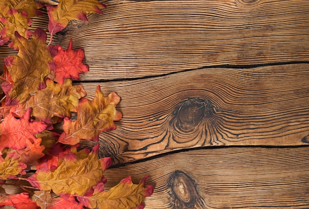 Kleurrijke herfstbladeren op een bruine houten achtergrond.