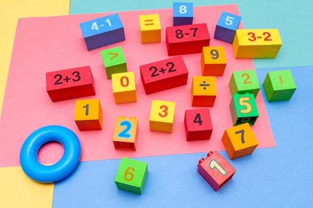 Kleurrijke het onderwijsspeelgoedkubussen van het kindjonge geitje met het patroonachtergrond van de aantallenwiskunde op de heldere achtergrond. plat leggen. jeugd kinderschoenen kinderen baby's concept.