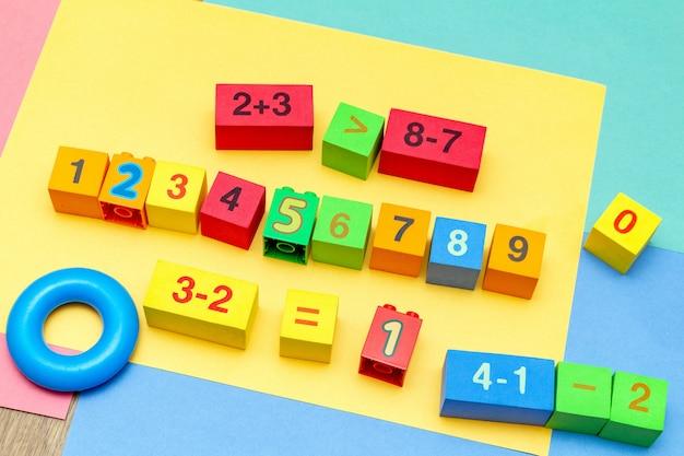 Kleurrijke het onderwijsspeelgoedkubussen van het kindjonge geitje met het patroonachtergrond van de aantallenwiskunde op de heldere achtergrond.