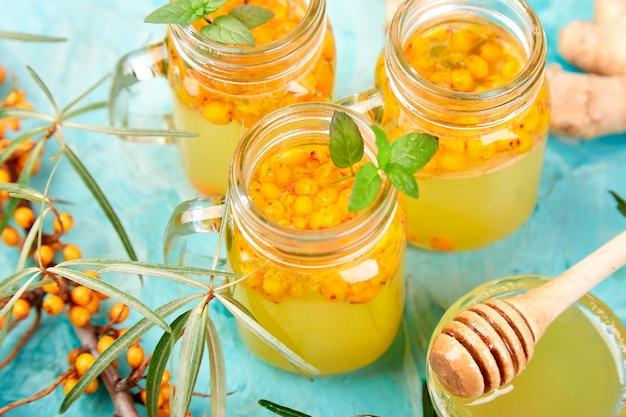 Kleurrijke hete duindoornthee met gember en honing
