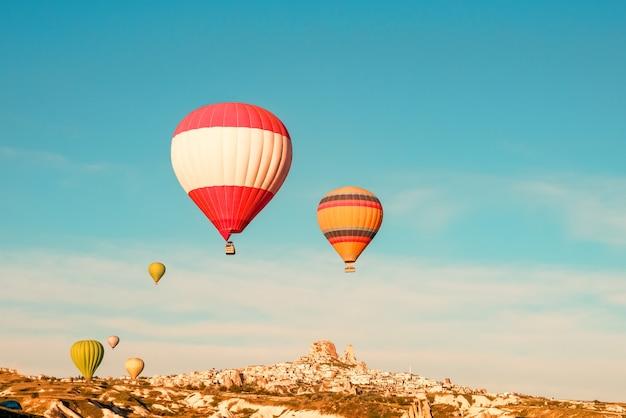 Kleurrijke hete lucht ballonnen vliegen in de buurt van uchisar kasteel bij zonsopgang, cappadocië, turkije