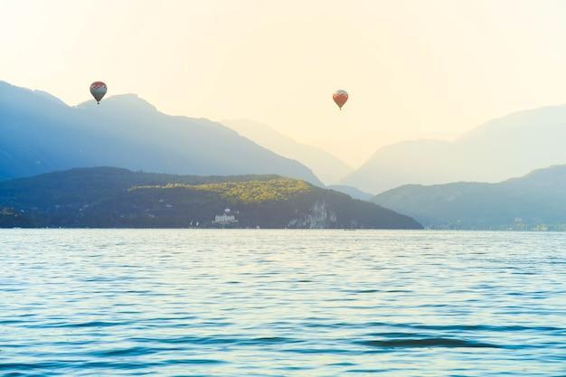 Kleurrijke hete lucht ballonnen vliegen over meer