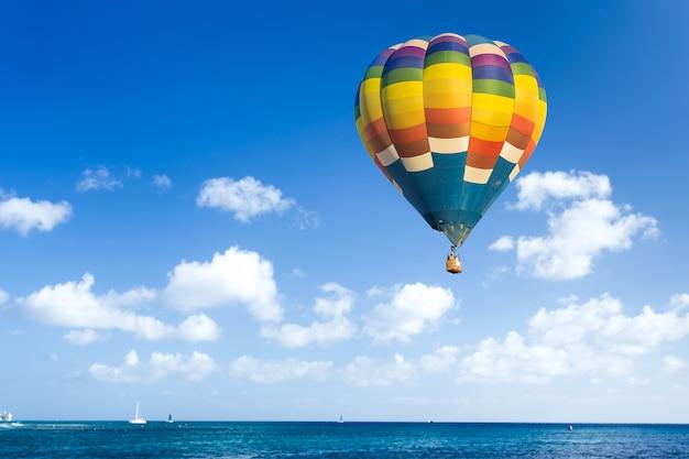 Kleurrijke hete luchtballon over de oceaan met blauwe hemel