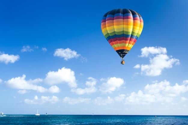 Kleurrijke hete luchtballon vliegt over de blauwe zee
