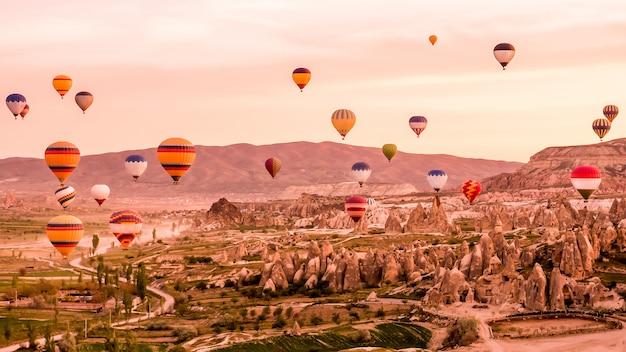 Kleurrijke hete luchtballons die over rotslandschap in cappadocia turkije vliegen