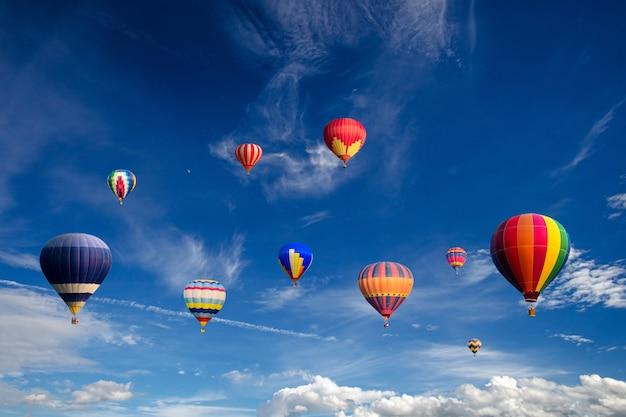 Kleurrijke hete luchtballons die over witte wolken en blauwe hemel vliegen.