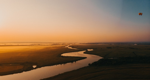 Kleurrijke heteluchtballon epische vliegen over de mist bij zonsopgang hooggelegen luchtfoto drone weids uitzicht