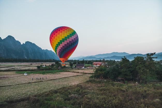 Kleurrijke heteluchtballon stijgt net op tijd op om de prachtige zonsondergang boven vang vieng in laos, zuidoost-azië te verkennen.