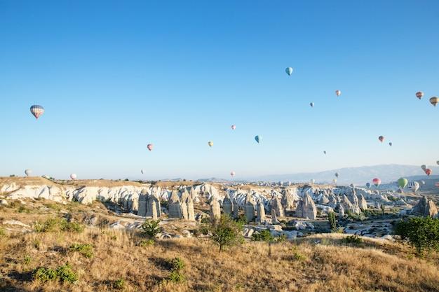 Kleurrijke heteluchtballonnen die over cappadocië vliegen