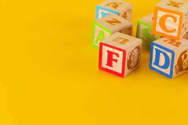 Kleurrijke houten blokken met letters op een gele kleurenachtergrond