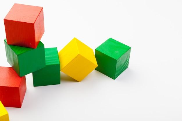 Kleurrijke houten bouwstenen die op witte achtergrond worden geïsoleerd