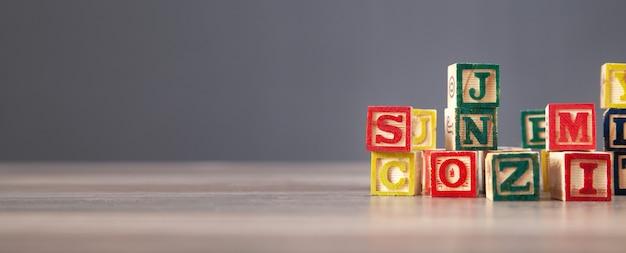Kleurrijke houten kubussen met letters op de houten tafel.
