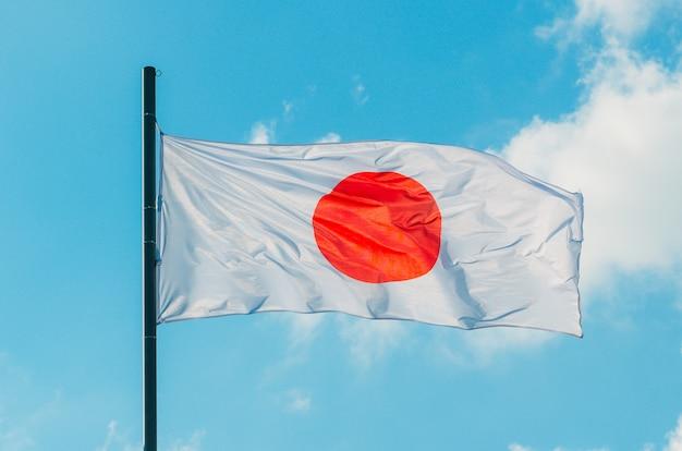 Kleurrijke japan vlag zwaaien op blauwe hemel.
