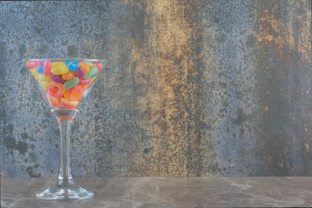 Kleurrijke jellybean snoepjes in glas over grijze achtergrond.